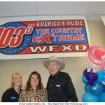 Dee Dee, Tina, and Elmer Aho Pose Below WFXD 1033 Country Extreme Banner
