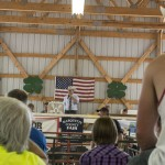 Auctioneer from the back of the packed barn during the livestock sale at the Marquette County Fair 2015