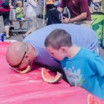 Family fun at the watermelon eating contest table.