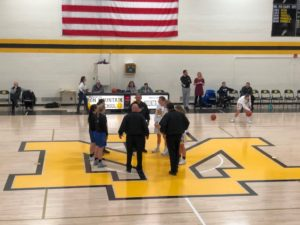 The Ishpeming Hematites girls basketball team captains watch the coin flip during their game against the Iron Mountain Mountaineers